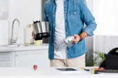 Photo cropped view of man holding electric mixer at kitchen