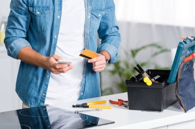 cropped view of man holding smartphone and credit card near tool box