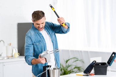 angry adult man screaming and holding mixer and hammer