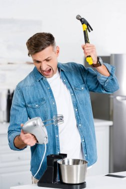 aggressive adult man screaming while holding mixer and hammer