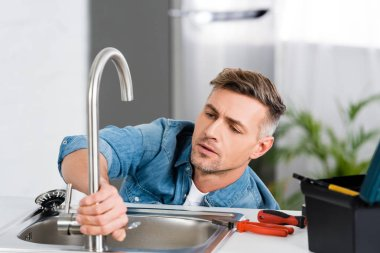 handsome man repairing faucet of kitchen sink