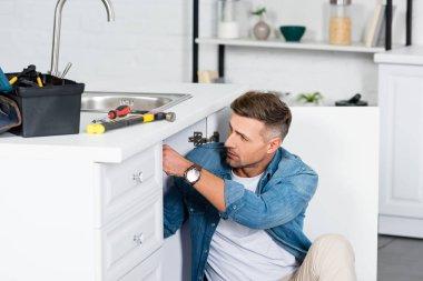 Handsome man repairing kitchen sink stock vector