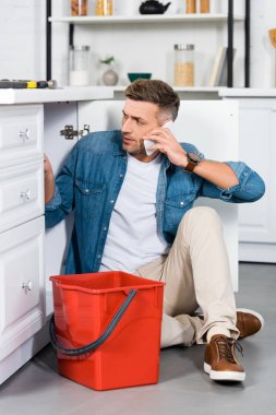 handsome man repairing kitchen sink and talking on smartphone