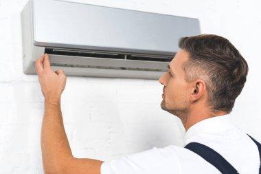 Handsome repairman fixing air conditioner stock vector
