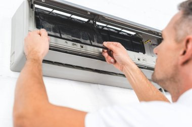 Close up view of man fixing filter of air conditioner stock vector