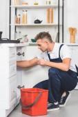 Fotografie pro dospělé opravář s červený plastový kbelík a opravy kuchyňského dřezu spanner