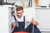 Nachdenklicher erwachsener Reparateur sitzt unter der Spüle und hält Rohre für Reparaturen in der Küche