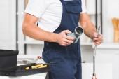 Ausgeschnittene Ansicht eines Reparateurs, der Rohre für die Reparatur von Küchenarmaturen hält