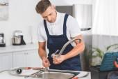 Nachdenklicher erwachsener Reparateur nimmt Küchenarmatur zur Reparatur ab