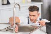Erwachsener Reparateur hält Rohr und Schraubenschlüssel bei Reparatur des Wasserhahns in der Küche