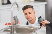 Photo thoughtful adult repairman holding pipes and tools while repairing faucet at kitchen