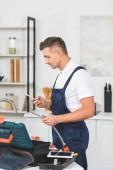Fotografia Profilo di adulto riparatore che tiene tubo per rubinetto della cucina riparare e usando smartphone