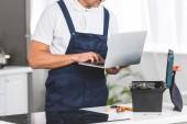 Fotografia vista potata del riparatore adulto usando il portatile durante il ripristino elettrico stufa in cucina