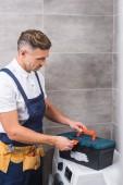 opravář v pásu nástroj zavřete okno nástroje po opravě pračka v koupelně