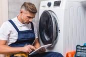 felnőtt műszerész csavarhúzó gazdaság, és segítségével digitális tábla, míg a fürdőszobában mosógép javítása