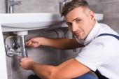 Photo adult repairman repairing sink at bathroom and looking at camera