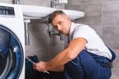 pro dospělé opravář sedí na podlaze a držení nástroje pro opravu v koupelně a při pohledu na fotoaparát