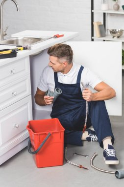 adult repairman with red plastic bucket holding pipes for repairing kitchen sink