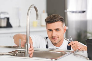 Smiling adult repairman holding pipe and spanner while repairing faucet at kitchen and looking at camera stock vector