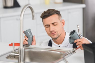 Thoughtful adult repairman holding pipes and tools while repairing faucet at kitchen stock vector