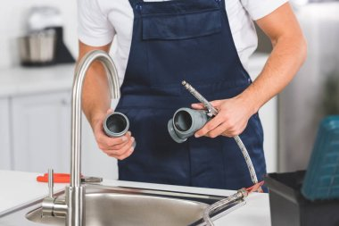 cropped view of repairman holding pipes and tools while repairing faucet at kitchen