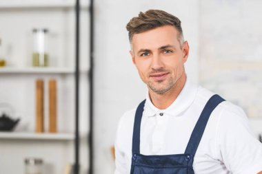 portrait of adult repairman in overall standing at kitchen and looking at camera