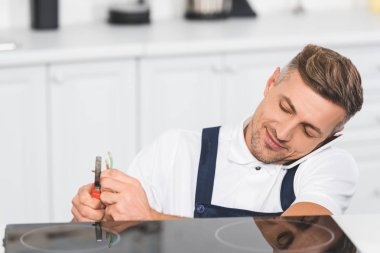 adult repairman talking on smartphone while repairing electric stove at kitchen