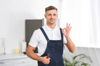 smiling adult repairman holding pliers while showing ok sign and looking at camera