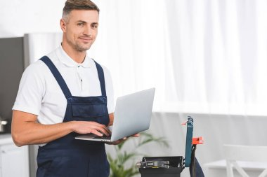 adult repairman holding laptop while standing at kitchen and looking at camera