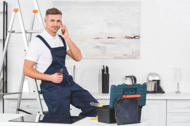smiling adult repairman sitting on ladder holding pliers and talking by smartphone at kitchen and looking at camera
