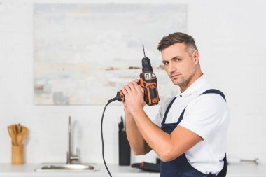 smiling adult repairman holding drill in hands like gun and looking at camera