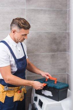 banyo, çamaşır makinesi onarımından sonra araçları kutusunu kapatmadan alet kemeri tamirci