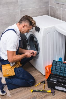 adult repairman working with screwdriver while repairing washing machine in bathroom