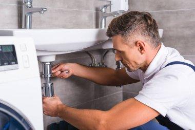 adult plumber fixing sink at bathroom