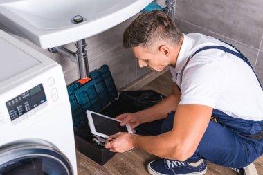 adult repairman sitting on floor and using digital tablet while repairing sink at bathroom
