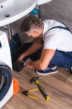 adult repairman sitting on floor and taking repair tools from box