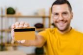 Selektivní fokus z kreditní karty v ruce veselý muž