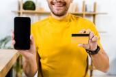 ritagliate la vista delluomo che tiene smartphone con lo schermo in bianco e carta di credito nelle mani