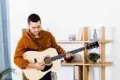 handsome musician playing acoustic guitar at home