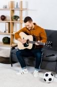 handsome musician in glasses playing acoustic guitar in living room