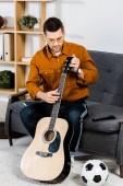 pohledný muž v brýlích sedí na pohovce a ladění akustická kytara doma