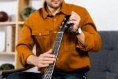 oříznutý pohled člověka ladění akustická kytara doma