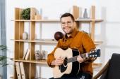 Fotografia uomo felice in vetri giocando chitarra acustica a casa