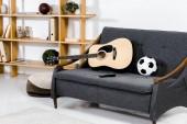 akusztikus gitár, a labda és a távirányító a kanapé modern nappali