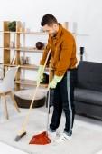 Fotografie pohledný muž, stojící v moderním obývacím pokoji a zametání podlahy