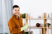 pohledný muž, stojící v moderním obývacím pokoji a drží láhev a usmívala se na kameru