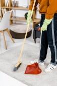 oříznutý pohled člověka stál v moderním obývacím pokoji a zametání podlahy