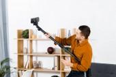schöner Mann in modernem Wohnzimmer steigt Staubsauger auf