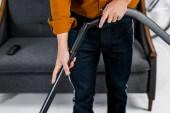 abgeschnittene Ansicht des Menschen in modernen Wohnräumen Putzboden mit Staubsauger