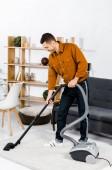 schöner Mann im modernen Wohnzimmer lächelt und putzt Haus mit Staubsauger
